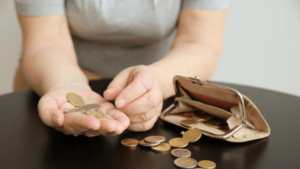 Frau zählt Geld aus Niedriglohn-Job